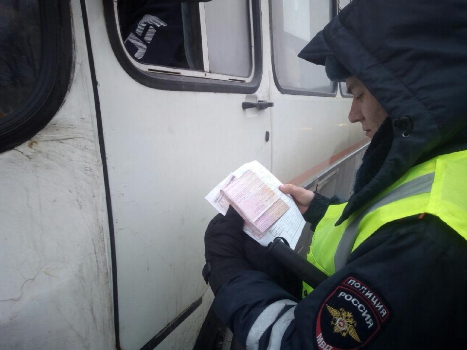 Сотрудник ГИБДД проверяет документы у водителя маршрутки